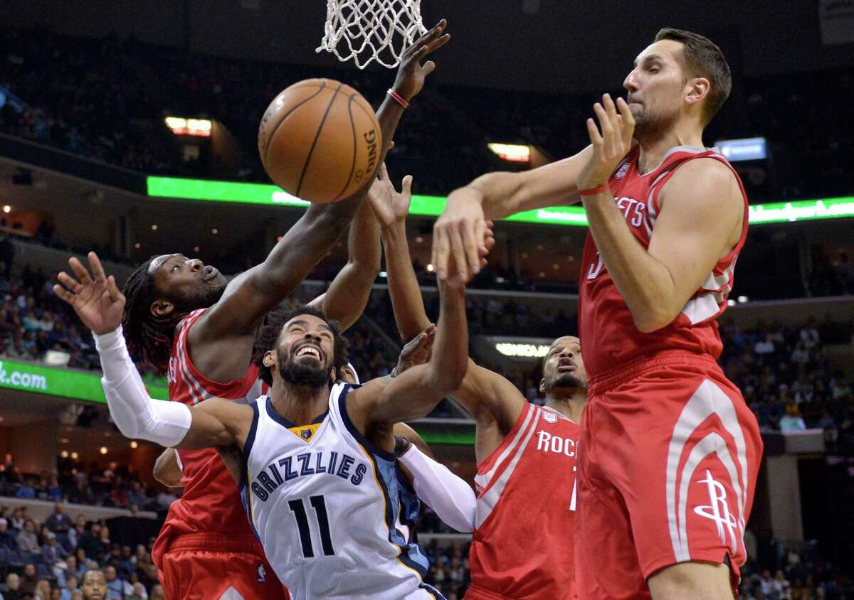 Memphis Grizzlies guard Mike Conley (11) shoots between Houston Rockets forwards Montrezl Harrell, Trevor Ariza and Ryan Anderson, from left, during the second half of an NBA basketball game Friday, Dec. 23, 2016, in Memphis, Tenn. The Grizzlies won 115-109.p (AP Photo/Brandon Dill)