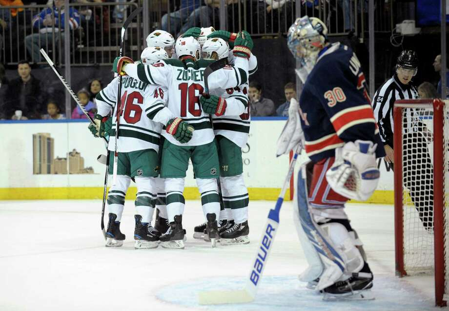 Minnesota Wild players celebrate a goal by Michael Granlund as New York Rangers goaltender Henrik Lundqvist stands in front of the net during the first period of an NHL hockey game Friday, Dec. 23, 2016, at Madison Square Garden in New York. (AP Photo/Bill Kostroun) ORG XMIT: MSG102 Photo: Bill Kostroun / FR51951 AP