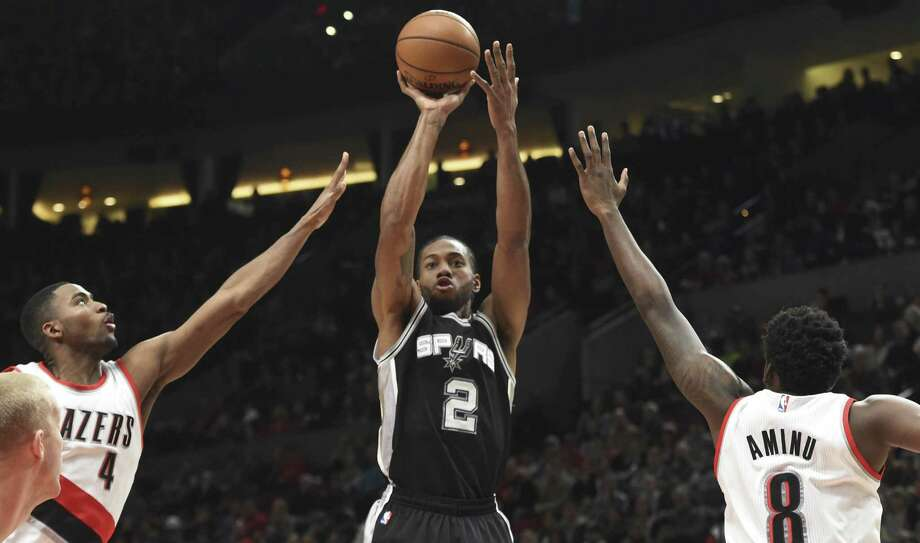 San Antonio Spurs forward Kawhi Leonard hits a shot between Portland Trail Blazers forwards Maurice Harkless and forward Al-Farouq Aminu, right, during the first half of an NBA basketball game in Portland, Ore., Friday, Dec. 23, 2016. AP Photo/Steve Dykes) Photo: Steve Dykes, FRE / Associated Press / FR155163 AP