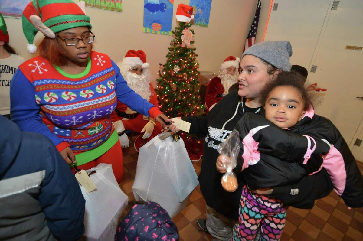Luceli Rivera is given a bag of toys and gifts for her family from elf, Sharlie Daniel, as South Norwalk residents Ernie and Martha Dumas and other volunteers distribute free Christmas gifts to needy families as part of their annual
