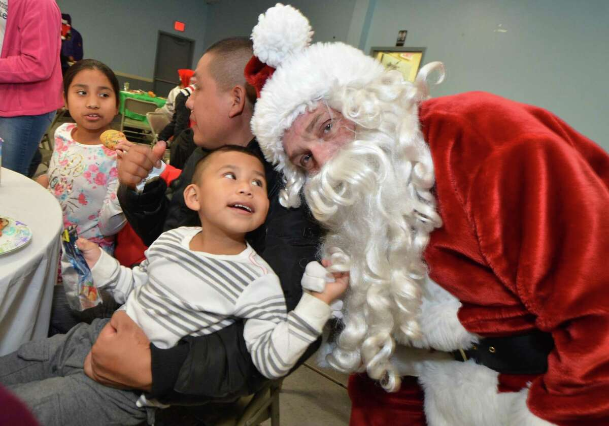 Angel Robles, 3, sits on the lap of his father Angel during a visit from Santa Claus, as South Norwalk residents Ernie and Martha Dumas and other volunteers distribute free Christmas gifts to needy families as part of their annual