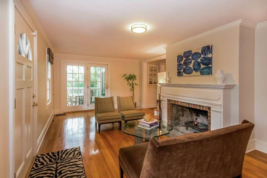 The formal living room has the home's only fireplace. It is a wide red brick fireplace that burns wood and French doors that lead to the wood deck on the rear of the house.