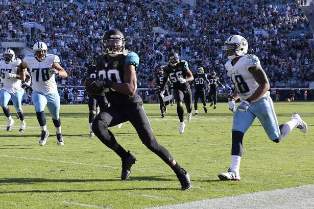 Jacksonville Jaguars cornerback Jalen Ramsey, front left, returns an interception for a touchdown against the Tennessee Titans' Rishard Matthews (18) during the second half of an NFL football game, Saturday, Dec. 24, 2016, in Jacksonville, Fla. (AP Photo/Gary McCullough)