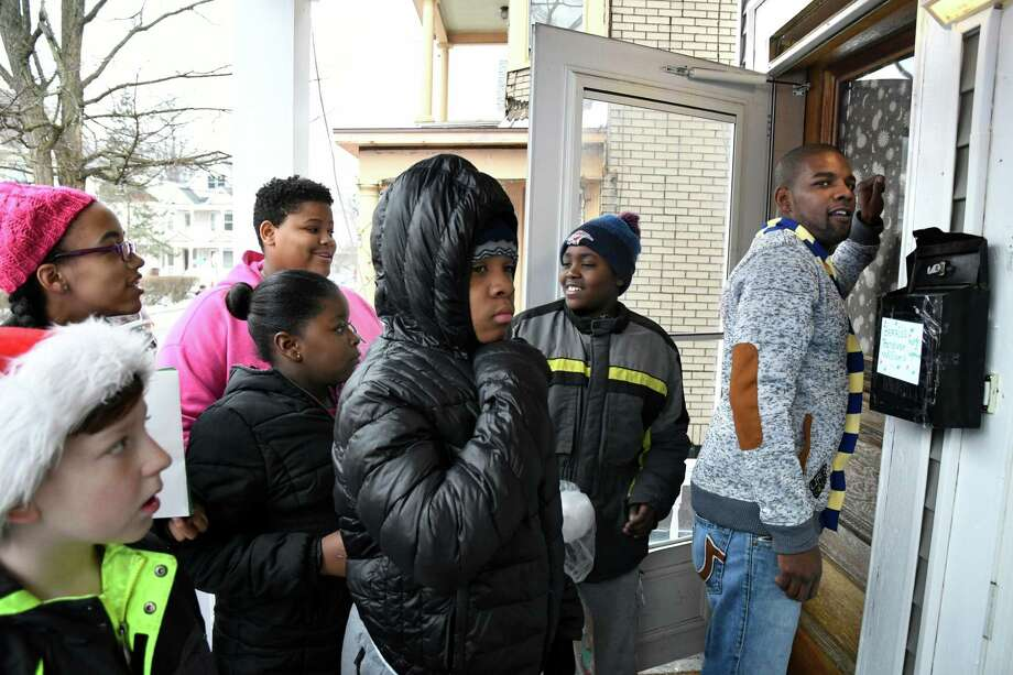 Nashawn Jones, right, joins other volunteers as he knocks on the door of family slated to receive gifts during the SaveOurStreets toy giveaway on Saturday, Dec. 24, 2016, Schenectady, N.Y. The community organization delivered toys from a school bus with a Schenectady Police escort on Christmas Eve. (Cindy Schultz / Times Union) Photo: Cindy Schultz / Albany Times Union