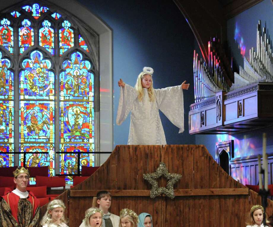 "At top, Ainsley Sahrbeck, 8, played the angel presiding over the nativity during the Christmas Eve Family Service at the First Congregational Church in Old Greenwich, Conn., Saturday, Dec. 24, 2016. Rev. Richard DenUyl, Jr., an inn keeper's son, gave the sermon telling stories about how his father always made sure there was room at their family inn and how First Congregational Church has the same philosophy, saying all are welcome. Craig Scott Symons, the music director at the church, who played organ duirng the service and led the choirs said ""we have been doing this service as long as I can remember. It is a great tradition that brings us, all of our families back together. It is wonderful."" Symons said that more than 40 kids participated in the nativity and the singing during the standing room only service. Photo: Bob Luckey Jr. / Hearst Connecticut Media / Greenwich Time"