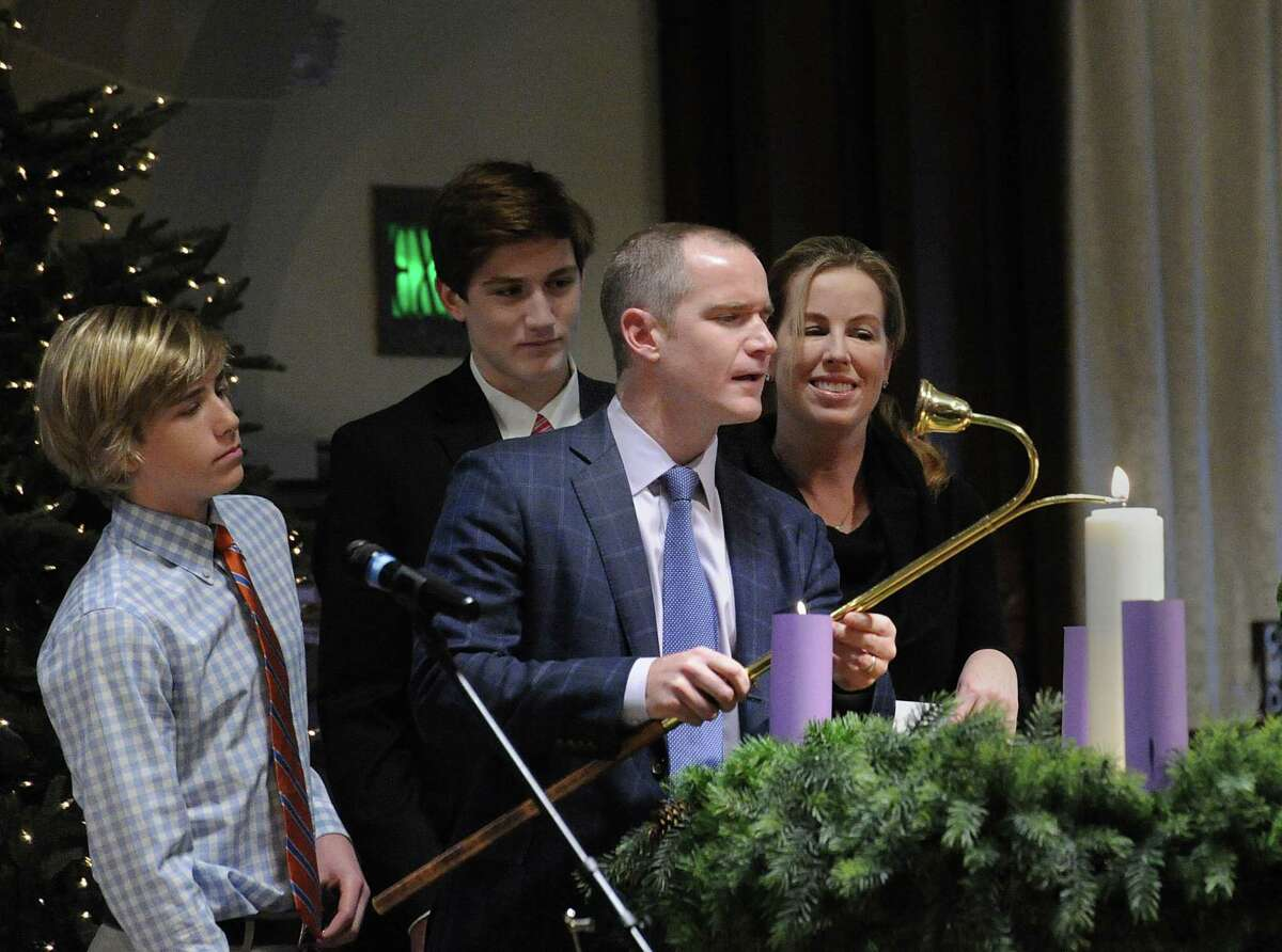 As his family looks on, Kevin Molloy, center, of Old Greenwich, lights the Christ candle during the Christmas Eve Family Service at the First Congregational Church in Old Greenwich, Conn., Saturday, Dec. 24, 2016. Rev. Richard DenUyl, Jr., an inn keeper's son, gave the sermon telling stories about how his father always made sure there was room at their family inn and how First Congregational Church has the same philosophy, saying all are welcome. Craig Scott Symons, the music director at the church, who played organ duirng the service and led the choirs said