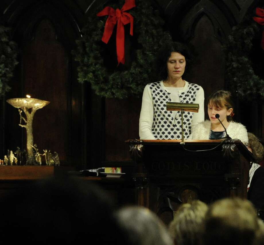 """With her mother Celeste Frye-Lintern at her side, Tallulah Lintern, 10, of Stamford recites a reading as part of a Christmas Eve service. The Unitarian Universalist Congregation in Stamford holds """"Fear Not Good News, Great Joy, For All People,""""  a """"Christmas Eve Carol"""" and candlelight service in Stamford  on Dec.24, 2016. Photo: Matthew Brown / Hearst Connecticut Media / Stamford Advocate"""