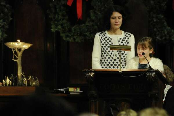 """With her mother Celeste Frye-Lintern at her side, Tallulah Lintern, 10, of Stamford recites a reading as part of a Christmas Eve service. The Unitarian Universalist Congregation in Stamford holds """"Fear Not Good News, Great Joy, For All People,""""  a """"Christmas Eve Carol"""" and candlelight service in Stamford  on Dec.24, 2016."""
