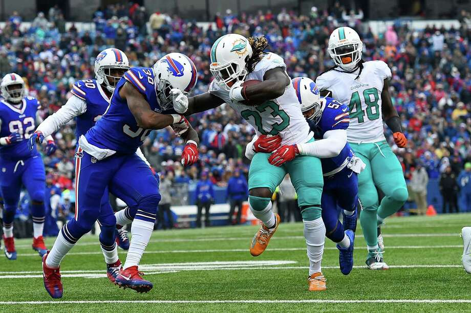 ORCHARD PARK, NY - DECEMBER 24:  Jay Ajayi #23 of the Miami Dolphins is tackled by Corey White #30 of the Buffalo Bills during the first half at New Era Stadium on December 24, 2016 in Orchard Park, New York.  (Photo by Rich Barnes/Getty Images) ORG XMIT: 681238619 Photo: Rich Barnes / 2016 Getty Images
