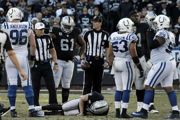Raiders quarterback Derek Carr (4) sits on the ground after being sacked on a play in the fourth quarter in which he was injured and carried off the field as the Oakland Raiders played the Indianapolis Colts at the Oakland Coliseum in Oakland, Calif., on Saturday, December 24, 2016. The Raiders won the game 33-25, but lost quarterback Derek Carr to injury.