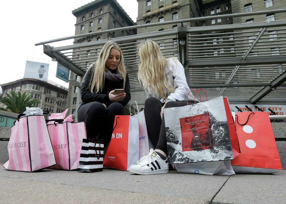 FILE - In this Nov. 25, 2016, file photo, Maddy, left, and her friend Maggie, sit with their shopping bags at Union Square in San Francisco. The holiday shopping season is losing some of its power in the year's sales. November and December now account for less than 21 percent of annual retail sales at physical stores, down from a peak of over 25 percent. The shift is in part because people are spreading out their shopping all year, demanding big discounts and spending more on events rather than more stuff. (AP Photo/Jeff Chiu, File) ORG XMIT: NY108 Photo: Jeff Chiu / Copyright 2016 The Associated Press. All rights reserved.