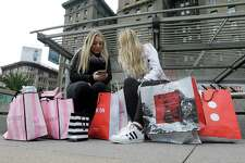 FILE - In this Nov. 25, 2016, file photo, Maddy, left, and her friend Maggie, sit with their shopping bags at Union Square in San Francisco. The holiday shopping season is losing some of its power in the year's sales. November and December now account for less than 21 percent of annual retail sales at physical stores, down from a peak of over 25 percent. The shift is in part because people are spreading out their shopping all year, demanding big discounts and spending more on events rather than more stuff. (AP Photo/Jeff Chiu, File) ORG XMIT: NY108