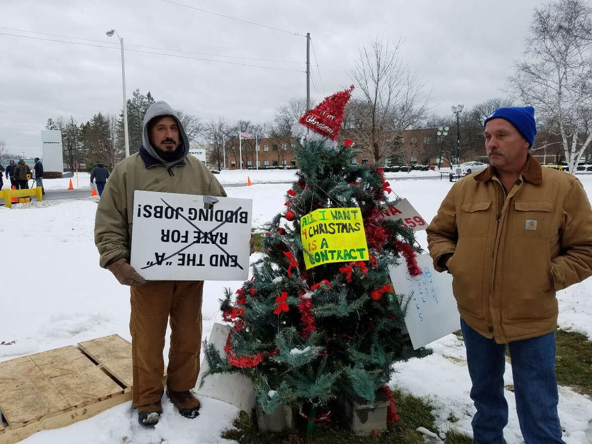 Striking Momentive Performance Materials workers Joe Giumarra, left, and Andy Reiniger, right, stand near a Christmas treat outside the Waterford chemical plant, where volatile chemicals are processed into sealants, adhesives and water repellents.