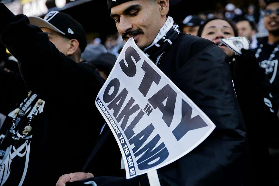 """A Raiders fan (declined name) holds a sign saying """"Stay in Oakland"""" during a football game between the Oakland Raiders and the Indiana Colts, in Oakland, Calif., on Saturday, Dec. 24, 2016. Photo: Gabrielle Lurie, The Chronicle"""
