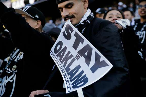 "A Raiders fan (declined name) holds a sign saying ""Stay in Oakland"" during a football game between the Oakland Raiders and the Indiana Colts, in Oakland, Calif., on Saturday, Dec. 24, 2016."