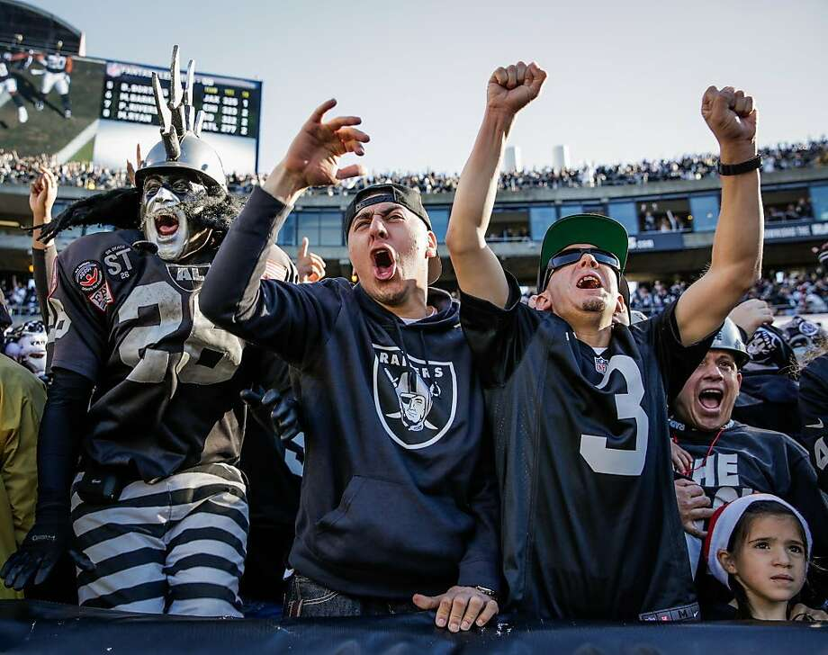 (l-r) Raiders fans Ray Perez, Paul Gonzalez and Javier Garcia cheer after the Raiders make a touchdown in the first half of a game between the Oakland Raiders and the Indiana Colts, in Oakland, Calif., on Saturday, Dec. 24, 2016. Photo: Gabrielle Lurie, The Chronicle