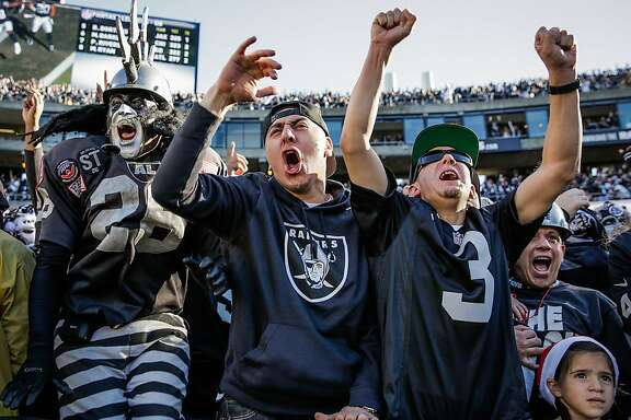 (l-r) Raiders fans Ray Perez, Paul Gonzalez and Javier Garcia cheer after the Raiders make a touchdown in the first half of a game between the Oakland Raiders and the Indiana Colts, in Oakland, Calif., on Saturday, Dec. 24, 2016.