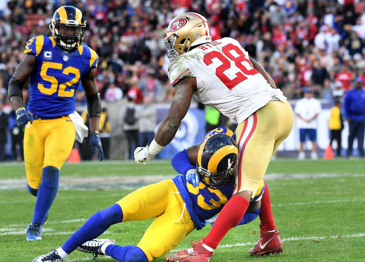 San Francisco 49ers running back Carlos Hyde (28) is knocked out of the game on this hit by the Los Angeles Rams' E.J. Gaines in the fourth quarter at the Los Angeles Coliseum on Saturday, Dec. 24, 2016. The 49ers won, 22-21. (Wally Skalij/Los Angeles Times/TNS)
