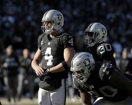 Derek Carr (4) with Jalen Richard (30) at the line of scrimmage before a play in the second quarter as the Oakland Raiders played the Indianapolis Colts at the Oakland Coliseum in Oakland, Calif., on Saturday, December 24, 2016. The Raiders won the game 33-25, but lost quarterback Derek Carr to injury.