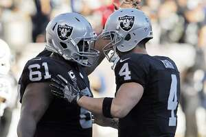 Derek Carr (4) celebrates a DeAndre Washington (33) touchdown with Rodney Hudson (61) in the third quarter as the Oakland Raiders played the Indianapolis Colts at the Oakland Coliseum in Oakland, Calif., on Saturday, December 24, 2016. The Raiders won the game 33-25, but lost quarterback Derek Carr to injury.