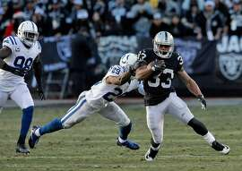 DeAndre Washington (33) gets by Mike Adams (29) for a short gain in the fourth quarter as the Oakland Raiders played the Indianapolis Colts at the Oakland Coliseum in Oakland, Calif., on Saturday, December 24, 2016. The Raiders won the game 33-25, but lost quarterback Derek Carr to injury.