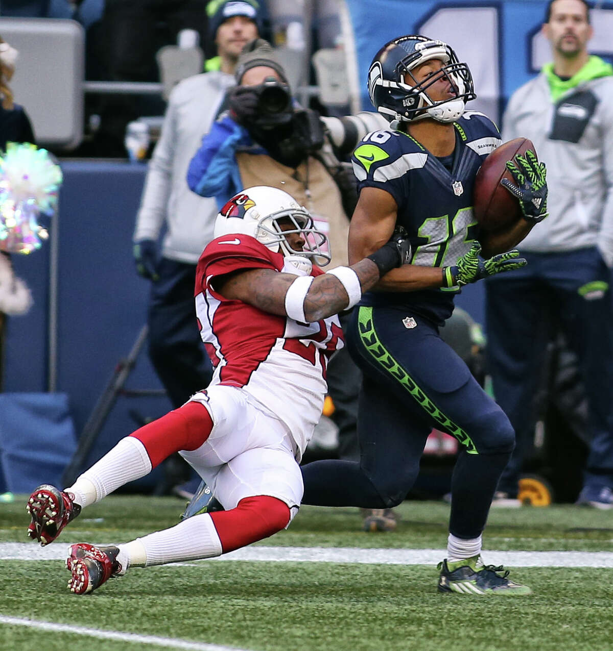 Cardinals cornerback Brandon Williams grabs on to Seahawks wide receiver Tyler Lockett, just before landing on his leg, during a tackle just short of a touchdown for Lockett. Lockett left the field on a cart. (Genna Martin, seattlepi.com)