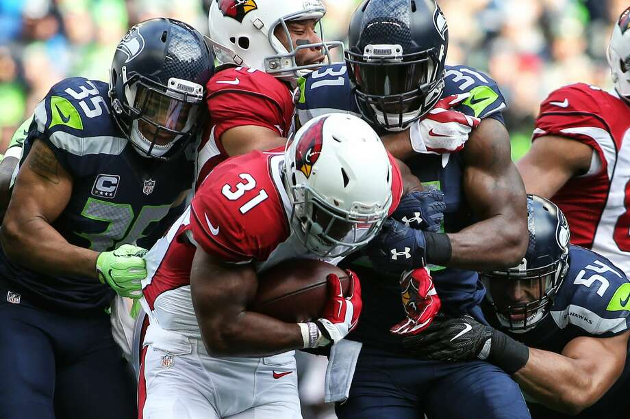 The Seahawks defense including Deshawn Shead (35), Kam Chancellor (31) and Bobby Wagner (54), take down Cardinals running back David Johnson during the first half of Seattle's game against Arizona, Saturday, Dec. 24, 2016 at CenturyLink Field.   (Genna Martin, seattlepi.com) Photo: GENNA MARTIN/SEATTLEPI.COM, G