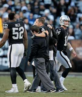 Matt McGloin (14) enters the game as Derek Carr (4) is carried off the field after fracturing his fibula in the fourth quarter as the Oakland Raiders played the Indianapolis Colts at the Oakland Coliseum in Oakland, Calif., on Saturday, December 24, 2016. The Raiders won the game 33-25, but lost quarterback Derek Carr to injury.