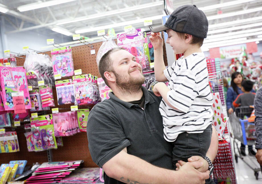 Conroe resident Chadoe Cullens smiles as his 6-year-old son Ethan steals his hat during a shopping trip on Friday at the Walmart off of Spring Cypress Road and SH 249. Photo: Michael Minasi, Staff / © 2016 Houston Chronicle