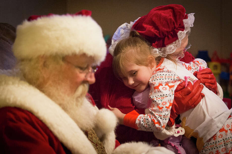 Olivia Morton, 5, hugs Mrs. Claus during the Take Home Santa event on Friday at the Rodriguez household in Conroe. Photo: Michael Minasi, Staff / © 2016 Houston Chronicle
