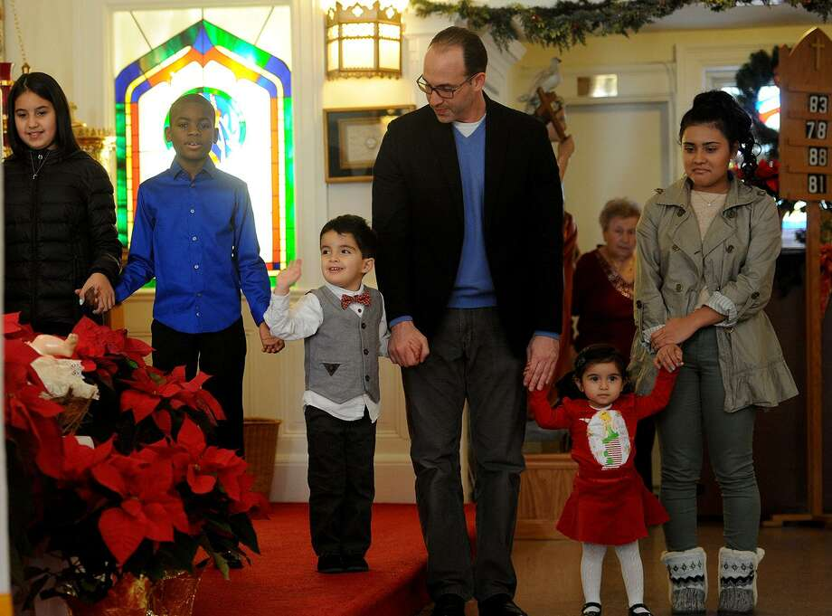 Franceso Chiodi, 4, of Shelton, waves to the deacons as he holds hands with his father, Phil Chiodi, during a Christmas Day service at St. Margaret's Shrine in Bridgport, Conn. on Sunday, December 25, 2016. At right are sisters Ariana Sandoval, 2, and Isabella Sandoval, of Ansonia. Photo: Brian A. Pounds / Hearst Connecticut Media / Connecticut Post