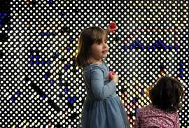 Logan Wrobel, 4, plays with Maya Patchen, 2, right, at the Light Wall in the Zim Zoom Family Room at the Contemporary Jewish Museum in San Francisco, Calif., on Sunday, December 25, 2016. The