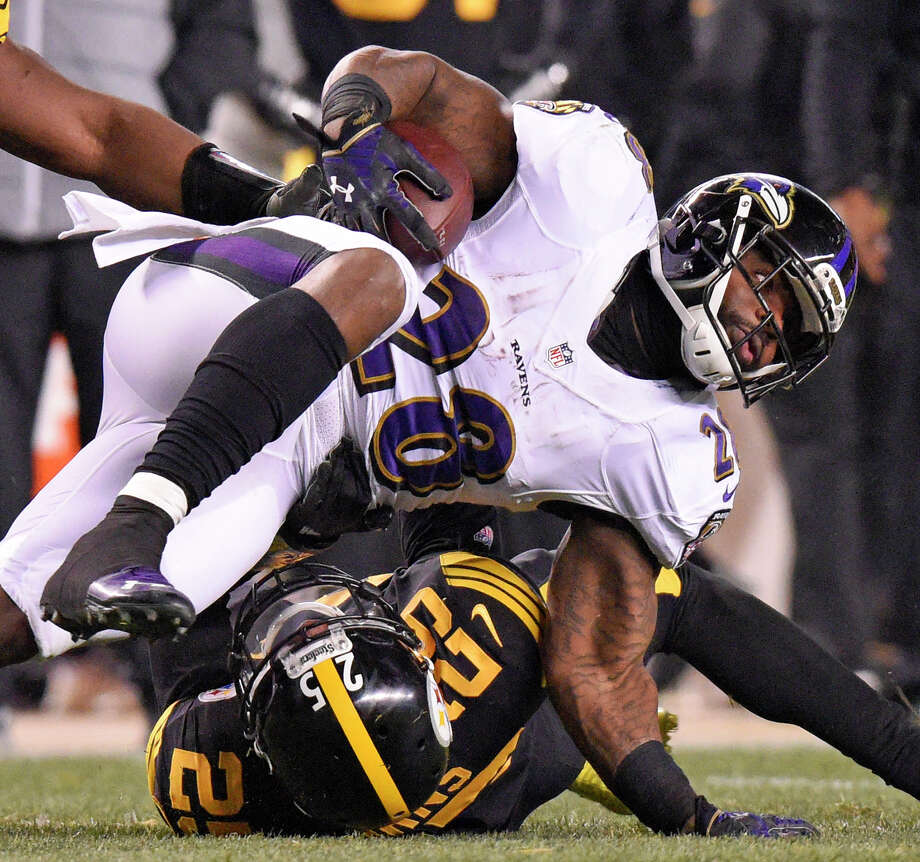 Baltimore Ravens running back Terrance West (28) tries for extra yardage after being tackled by Pittsburgh Steelers cornerback Artie Burns (25) during the first half of an NFL football game in Pittsburgh, Sunday, Dec. 25, 2016. (AP Photo/Don Wright) Photo: Don Wright, FRE / FR87040 AP