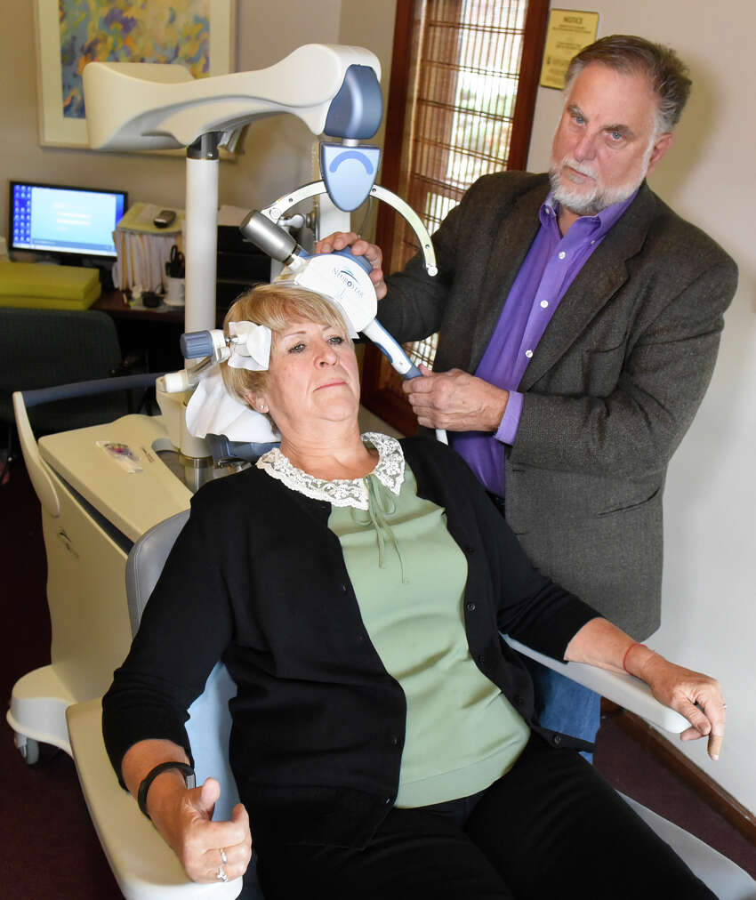 Dr. Edward Valentine, right, demonstrates Transcranial Magnetic Stimulation with his patient Colleen Casey of Delhi on Wednesday, Oct. 26, 2016, at Mohawk Hudson TMS Center in Gloversville, N.Y. The procedure is an FDA-approved depression treatment. (Cindy Schultz / Times Union)