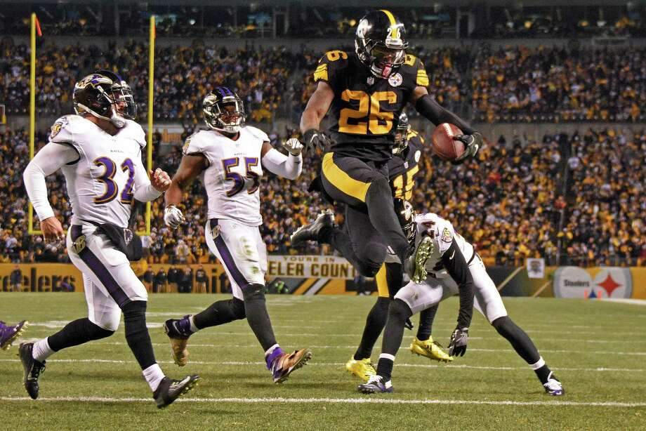 Pittsburgh Steelers running back Le'Veon Bell (26) leaps into the end zone ahead of Baltimore Ravens strong safety Eric Weddle (32) for a touchdown during the second half of an NFL football game in Pittsburgh, Sunday, Dec. 25, 2016. (AP Photo/Don Wright) ORG XMIT: PAGP126 Photo: Don Wright / FR87040 AP
