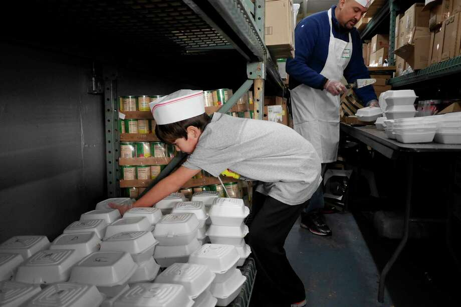Patrick Gauna, 8, left, and his father, Bernardo Gauna of Albany cut up pies and place them into containers for the takeout meals at the Capital City Rescue Mission on Sunday, Dec. 25, 2016, in Albany, N.Y.   (Paul Buckowski / Times Union) Photo: PAUL BUCKOWSKI / 20039225A