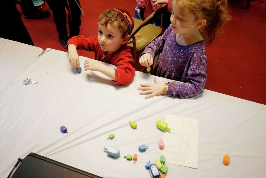 Leibel Serebryanski, 3, left, and his sister Fraida Serebryanski, 7, of Albany attempt to see how long they can spin a dreidel for during the Grand Hanukkah Chinese Buffet at the Beth Tephilah Synagogue on Sunday, Dec. 25, 2016, in Troy, N.Y.  This is the first year the synagogue has held the event.  The synagogue is also hosting a menorah lighting ceremony this week from Monday through Thursday at Monument Square in downtown Troy.  The event will being at 5:00pm each night.  The synagogue will honor different groups each night, with teachers being honored Wednesday night and veterans being honored Thursday night.  (Paul Buckowski / Times Union) Photo: PAUL BUCKOWSKI / 20039199A