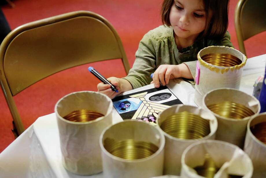 Esther Mathless, 5, of Albany colors a picture of a menorah during the Grand Hanukkah Chinese Buffet at the Beth Tephilah Synagogue on Sunday, Dec. 25, 2016, in Troy, N.Y.  This is the first year the synagogue has held the event.  The synagogue is also hosting a menorah lighting ceremony this week from Monday through Thursday at Monument Square in downtown Troy.  The event will being at 5:00pm each night.  The synagogue will honor different groups each night, with teachers being honored Wednesday night and veterans being honored Thursday night.  (Paul Buckowski / Times Union) Photo: PAUL BUCKOWSKI / 20039199A