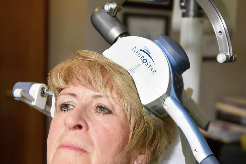 Patient Colleen Casey of Delhi demonstrates Transcranial Magnetic Stimulation on Wednesday, Oct. 26, 2016, at Mohawk Hudson TMS Center in Gloversville, N.Y. The procedure is an FDA-approved depression treatment. (Cindy Schultz / Times Union)