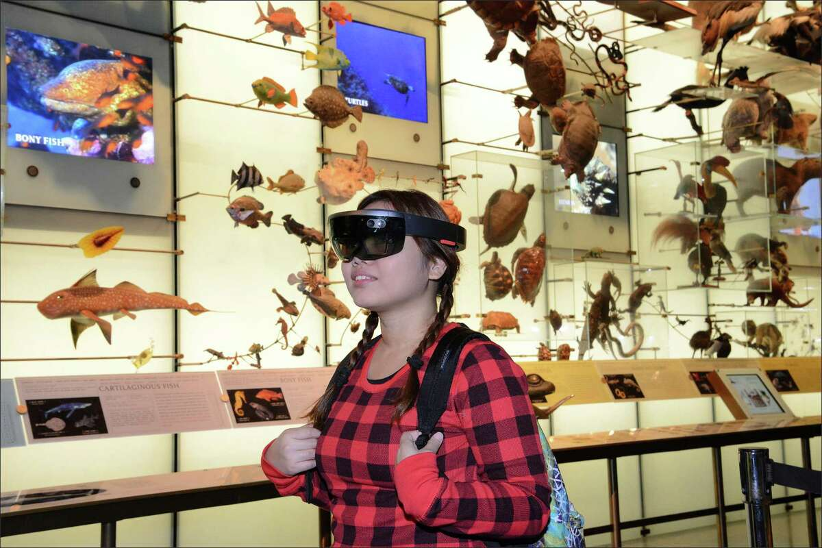 In this Dec. 13, 2016 photo provided by the American Museum of Natural History, a visitor at the museum in New York experiences 'AR Shark,' a prototype augmented reality program that overlays CT scan data on a Mako shark model in the Hall of Biodiversity. Museums working to present exciting and meaningful exhibits are increasingly relying on technology. (Roderick Mickens/American Museum of Natural History via AP) ORG XMIT: NYR304