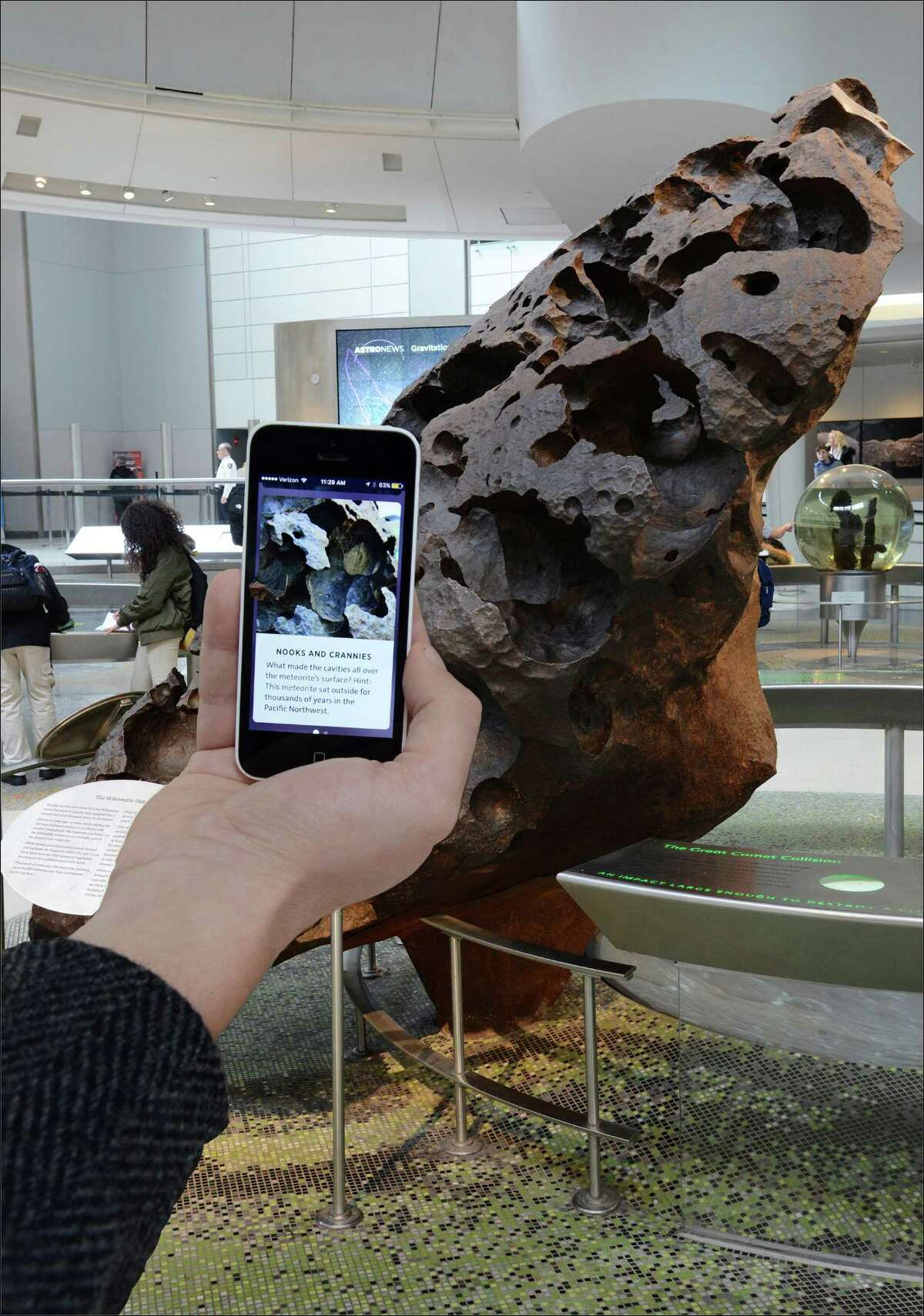 In this Dec. 12, 2016 photo provided by the American Museum of Natural History, a visitor uses the museum's flagship app Explorer which acts like a virtual curator, teaching visitors about the surprising facts and stories, near the Willamette Meteorite at the museum in New York. Museums working to present exciting and meaningful exhibits are increasingly relying on technology. (Roderick Mickens/American Museum of Natural History via AP) ORG XMIT: NYR305