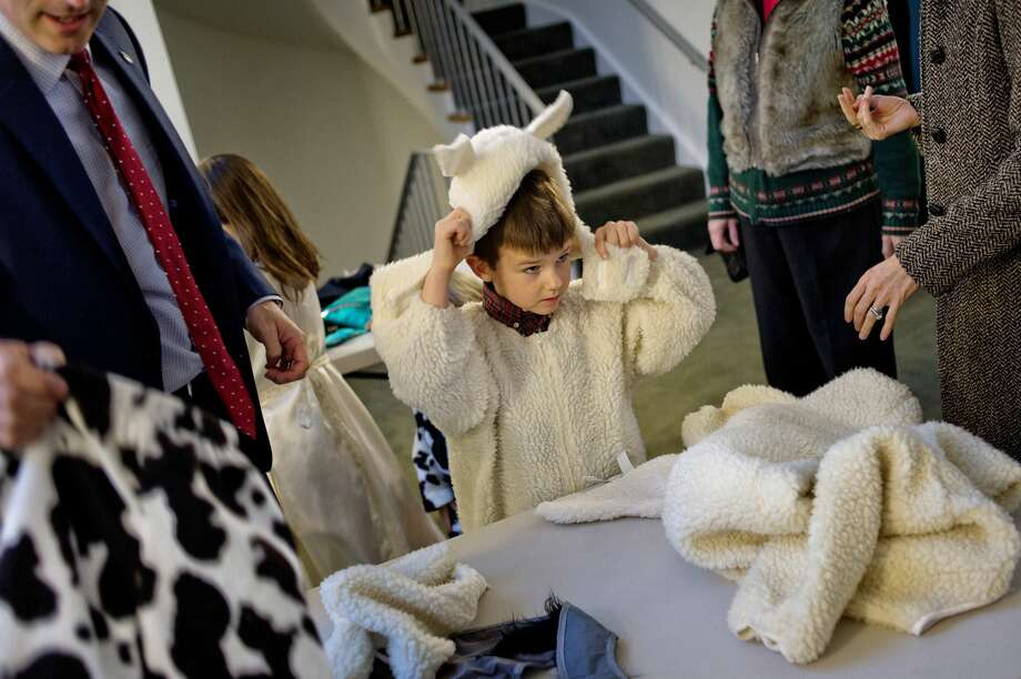 Nicholas Agostinelli, 6, puts on a sheep costume before the start of the unrehearsed Christmas pageant on Saturday at the Memorial Presbyterian Church in Midland. Children from the congregation helped act out the story of the birth of Jesus. Photo: NICK KING | Nking@mdn.net