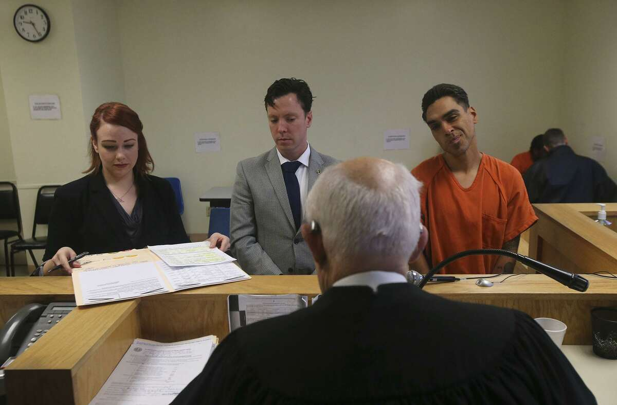A defendant (right) appears Friday December 9, 2016 in jail court, also known as Auxiliary Court, at the Bexar County Jail. On the left is prosecutor Holly Lovett in the center is defense attorney Ryan Boyer and the judge (facing away) is Olin Strauss.
