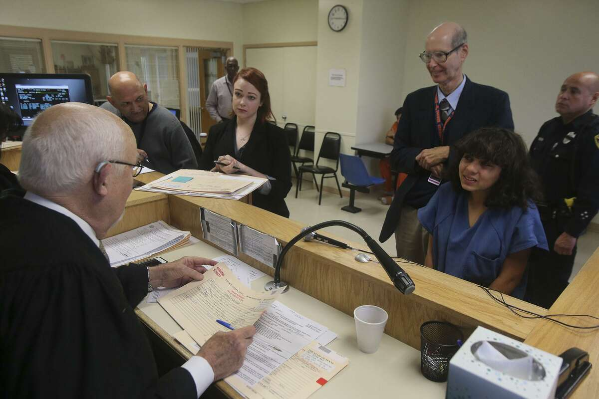 """Visiting Judge Olin Strauss speaks to a defendant standing in front of her attorney, Jim Oltersdorf, at """"jail court"""" at the Bexar County Adult Detention Center."""