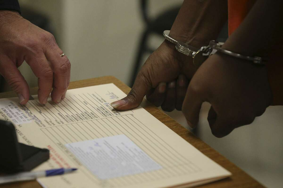 A defendant (right) is fingerprinted Friday December 9, 2016 in jail court, also known as Auxiliary Court, at the Bexar County Jail. Presiding at the hearing was Judge Olin Strauss.