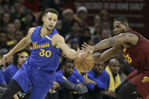 Golden State Warriors' Stephen Curry, left, and Cleveland Cavaliers' Tristan Thompson battle for a loose ball in the first half of an NBA basketball game, Sunday, Dec. 25, 2016, in Cleveland. (AP Photo/Tony Dejak)