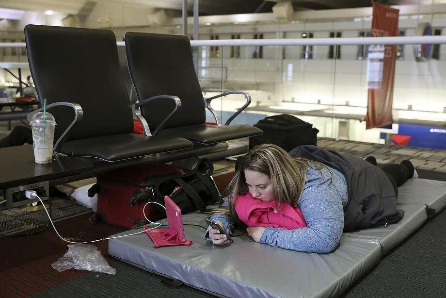 Chelsey Kalmback waits for a rescheduled flight to North Dakota at Minneapolis-Saint Paul International Airport. Photo: Anthony Souffle, Associated Press