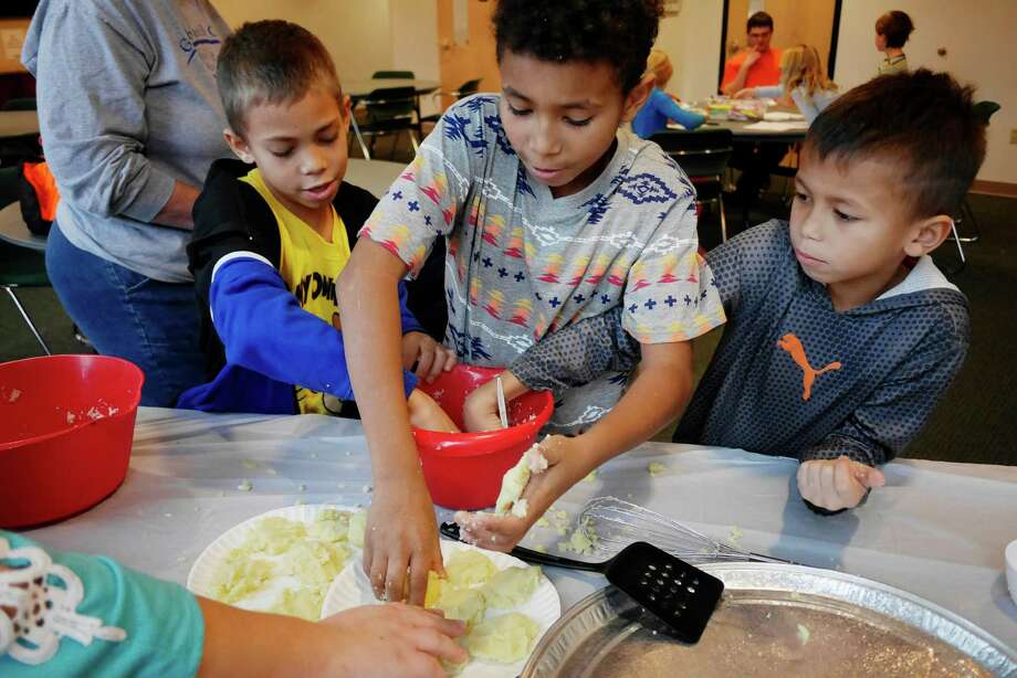 Brothers, Xavjon Arroyo, 8, left, Xaul Arroyo, 10, center, and Xajeno Arroyo, 6, of Schenectady make latkes at the Latke Making Extravaganza at the Schenectady Jewish Community Center on Monday, Dec. 26, 2016, in Schenectady, N.Y.  The center is opening its facility to the community allowing free access to the fitness center, pool and group classes for Hanukkah through Sunday, Jan. 1st.  The center is also hosting special events for the week, Hanukkah bingo and dinner Tuesday evening, senior lunch and family yoga on Wednesday, family zumba class on Thursday, Hanukkah crafts on Friday and a youth New Year's Eve party on Saturday.  The center will also host a menorah lighting each night of the holiday at 5:30pm.   (Paul Buckowski / Times Union) Photo: PAUL BUCKOWSKI / 20039200A