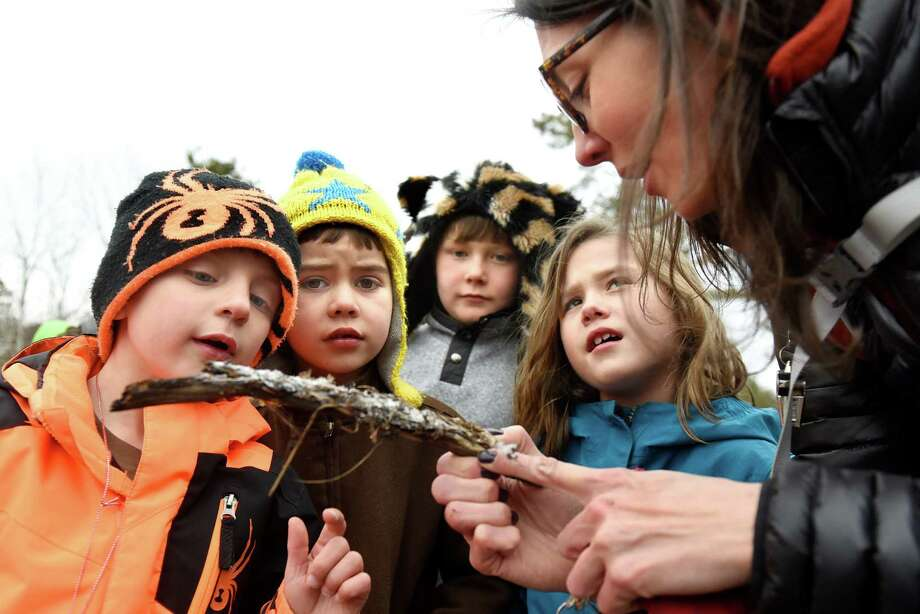 Outreach coordinator Grace Barber, right, holds a branch with ice crystals for children to examine during a Crystal Lab school-break program on Monday, Dec. 26, 2016, at the Pine Bush Discovery Center in Albany, N.Y. From left are Tyler Brown, 6, Hugo Hickey, 6, his brother Thomas Hickey, 8, and Lorenza Maylock, 7. This week's science series includes Microscope Magic on Thursday and Owl Investigation on Friday. (Cindy Schultz / Times Union) Photo: Cindy Schultz / Albany Times Union