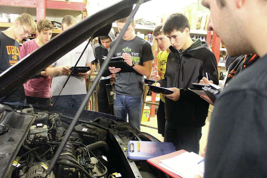 To help with the car repair, students went out to the bus garage to learn about changing a tire, jump starting a car and checking fluid levels.